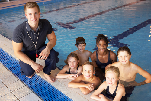 swim team in water with coach nearby