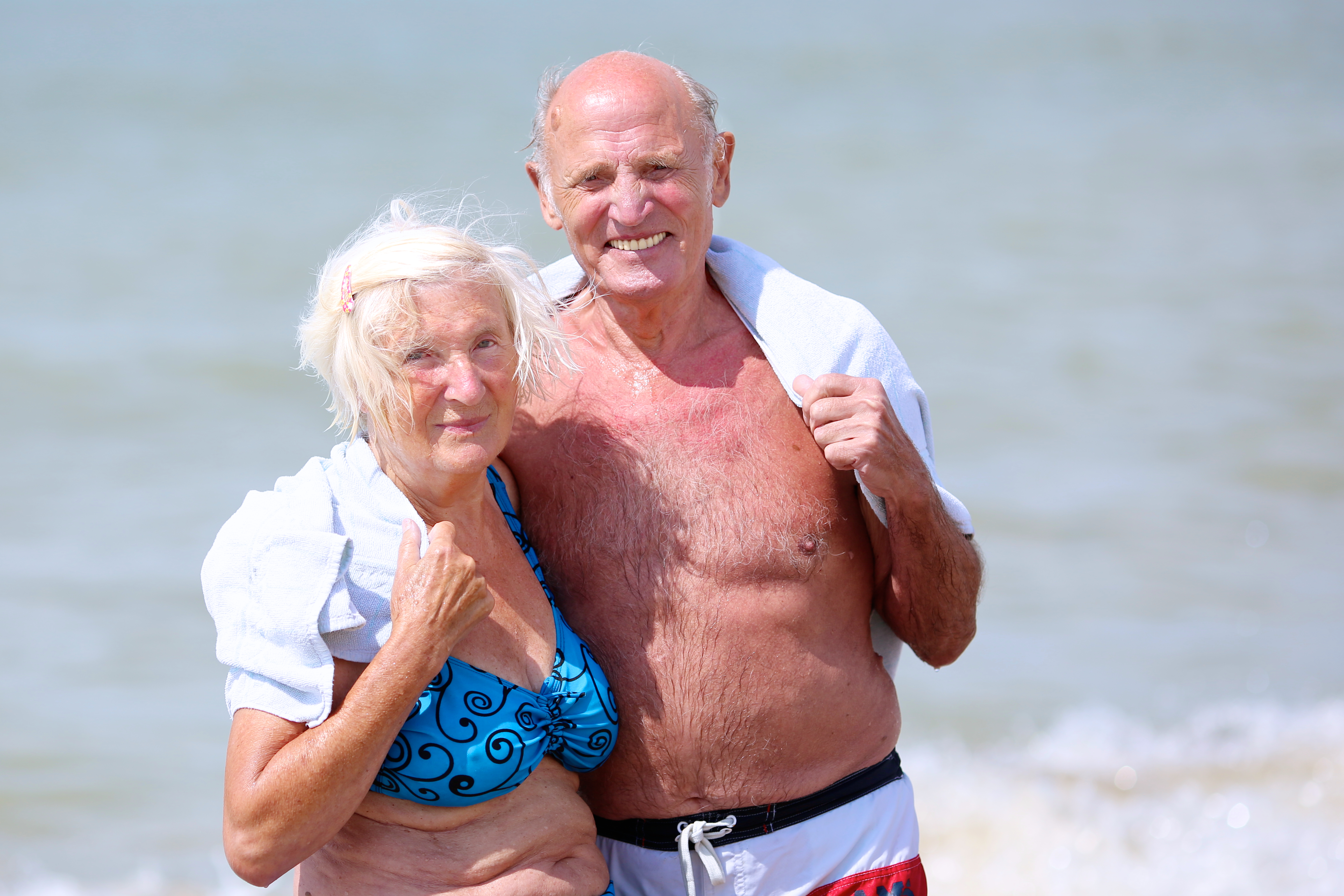 elderly couple on the beach after the polar bear plunge wrapped in a custom woven towel