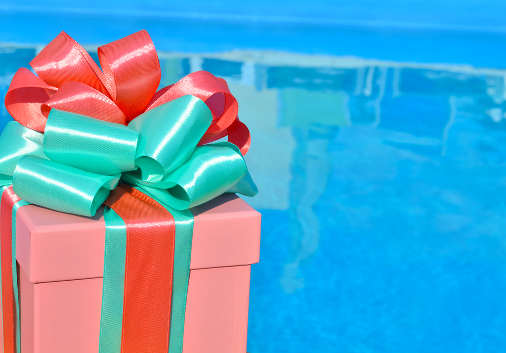 Christmas gift box against background of the blue pool
