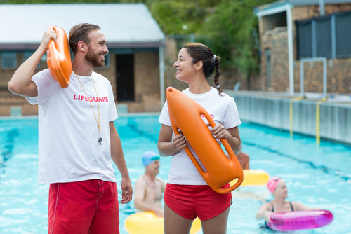 Male and female lifegaurd talking by outside pool