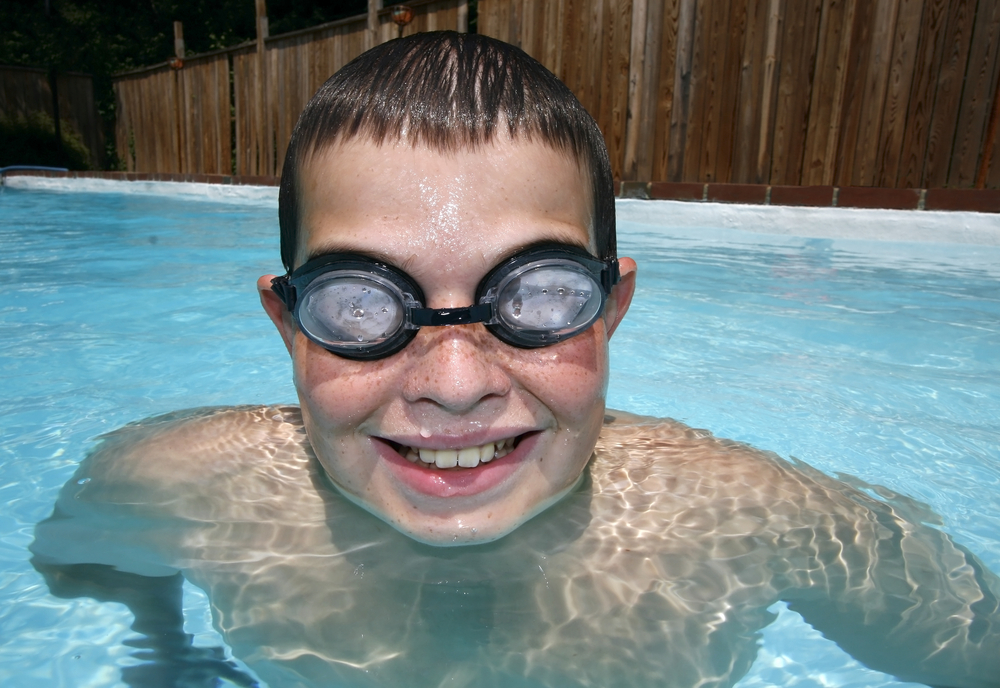 close-up of young boy in swimming pool with goggles