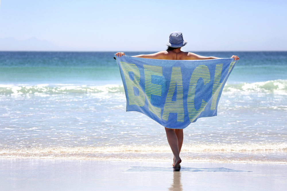 Woman walking with a towel around her on a pristine beach with the word BEACH spelled out on the towel.